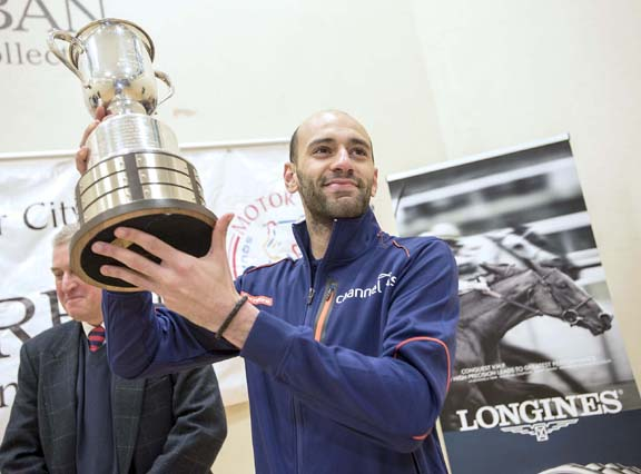 MCO champion Marwan ElShorbagy of Egypt hoists the hardware after defeating Paul Coll (New Zealand in the final. ElShorbagy also won a Longines watch from Greenstone Jewelers. (Photo by Bryan Mitchell for MCO)
